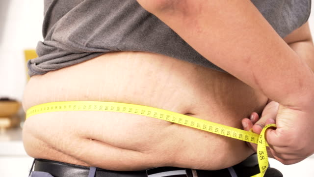 close-up front view: overweight man measuring his belly over 100 centimetre - largo descrizione generale video stock e b–roll