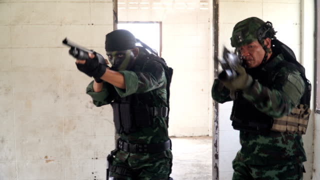 close-up front view: two fully Equipped and Armed Soldiers patrol in unknown house