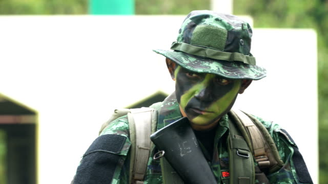 close-up: fully equipped and face-camouflaged senior soldier with his gun - military recruit stock videos & royalty-free footage
