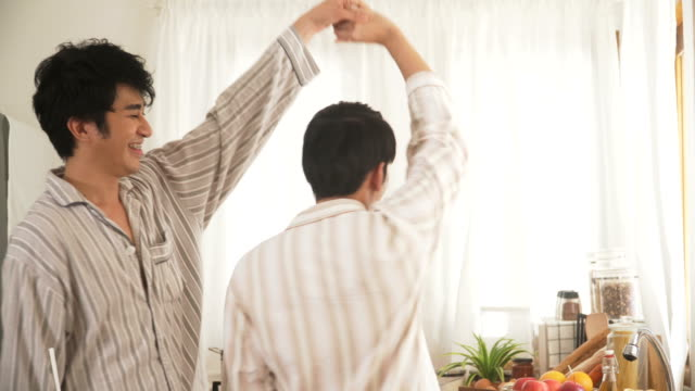 close-up: gay couple dancing in the modern kitchen after they wake up in morning