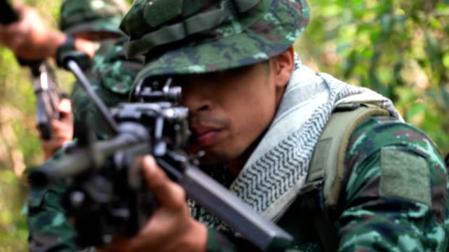 close-up gesture of Fully Equipped and Armed Soldiers are patrolling to tropical forest