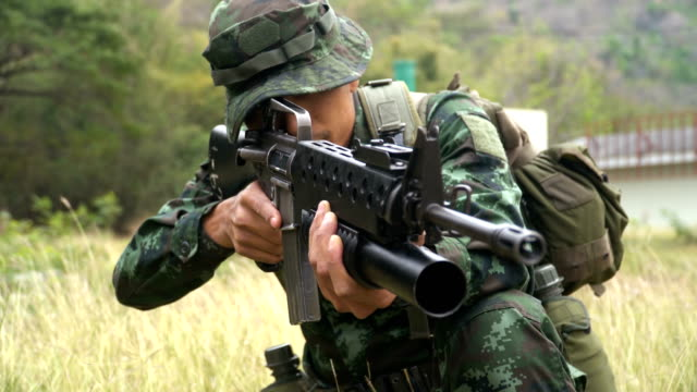 close-up: gesture of fully equipped and armed soldiers while sittingand be ready to fight