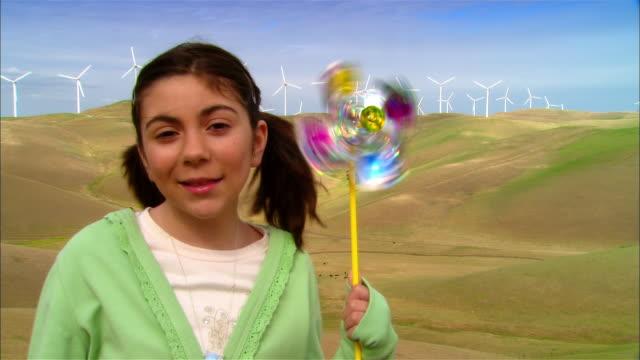 vídeos y material grabado en eventos de stock de close-up girl holding pinwheel in grassy field near wind turbines on hillside / livermore, california, usa - analógico