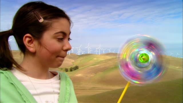 close-up girl holding pinwheel in grassy field near wind turbines on hillside / livermore, california, usa - girandola video stock e b–roll