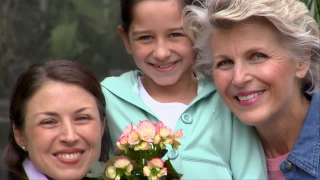 vidéos et rushes de close-up girl holding potted flower outside greenhouse with mother and grandmother/ san antonio, texas, usa - sourire à pleines dents