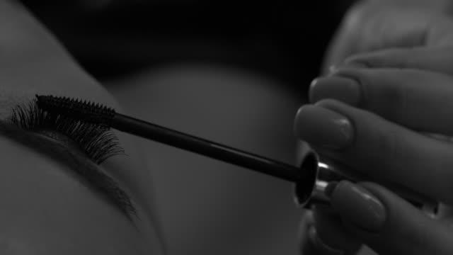 クローズアップの女の子は片目にマスカラでまつげを描きます。メイクアップ。 - 絵画モデル点の映像素材/bロール