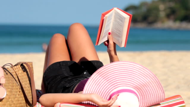 close-up, girl reading on the beach and relax - summer reading stock videos & royalty-free footage