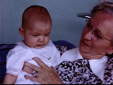 vidéos et rushes de 1950 close-up grandmother holding baby and smiling / california, usa  - grand mère