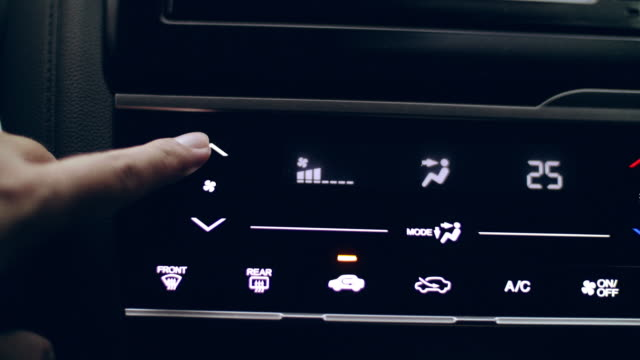 vídeos de stock e filmes b-roll de close-up hand adjusting button control air conditioning on a vehicle's dashboard - câmara à mão
