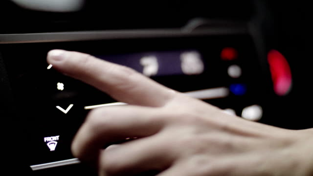 close-up hand adjusting button control air conditioning on a vehicle's dashboard - dashboard stock videos & royalty-free footage