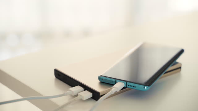 closeup hand charging adaptor to mobile smart phone into power bank. - computer cable stock videos & royalty-free footage