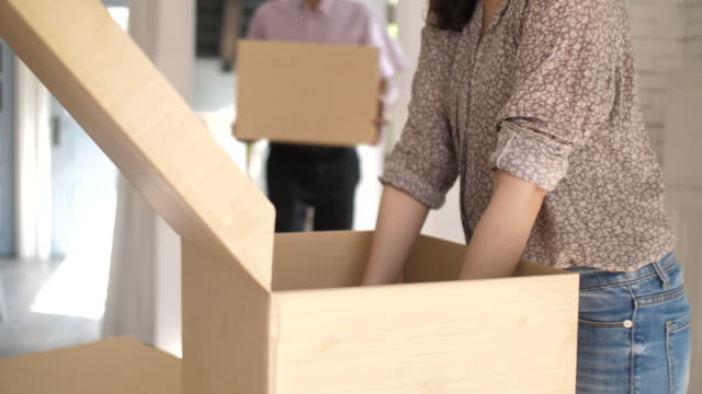 close-up hand couple carrying moving boxes and unpacking after moving into their new home - relocation stock videos & royalty-free footage
