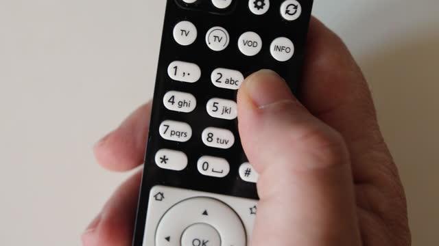närbild hand hålla fjärrkontrollen isolerade på vit bakgrund - nummer 8 bildbanksvideor och videomaterial från bakom kulisserna