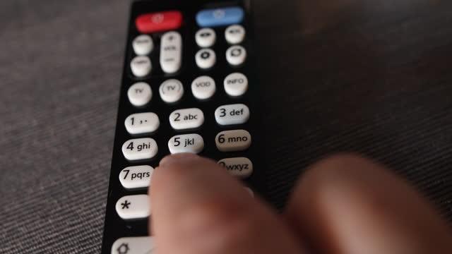närbild hand hålla fjärrkontrollen isolerade på vit bakgrund - nummer 6 bildbanksvideor och videomaterial från bakom kulisserna