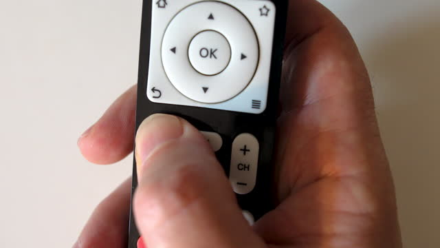 close-up hand holding remote control isolated on white background - remote control stock videos & royalty-free footage