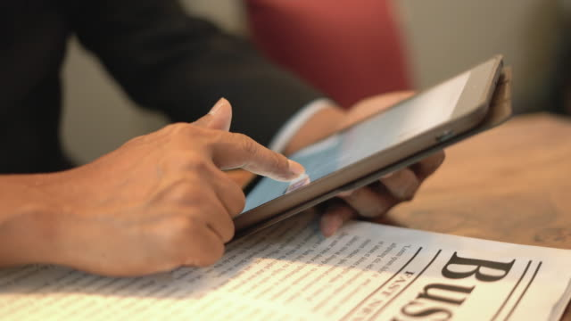 close-up hand of business man using his tablet in a cafe. - paper stock videos & royalty-free footage