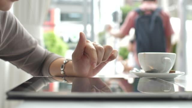 vídeos y material grabado en eventos de stock de mano de mano de la mujer de primer plano con tableta digital en café café - periódico