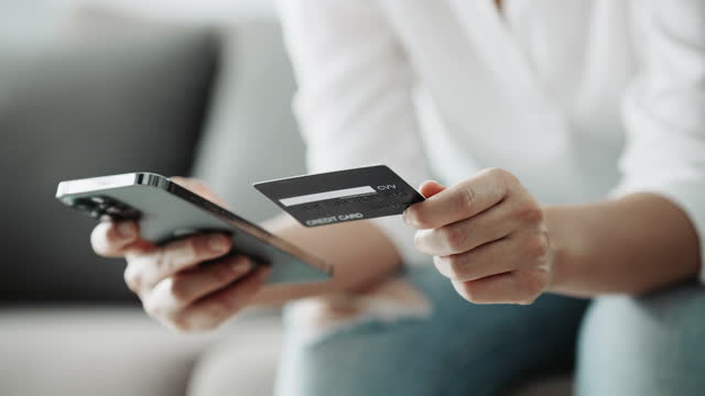close-up hand of woman is shopping online using a smartphone with credit card - playing card stock videos & royalty-free footage