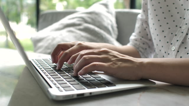 close-up hand of woman using laptop at home - over the shoulder stock videos & royalty-free footage