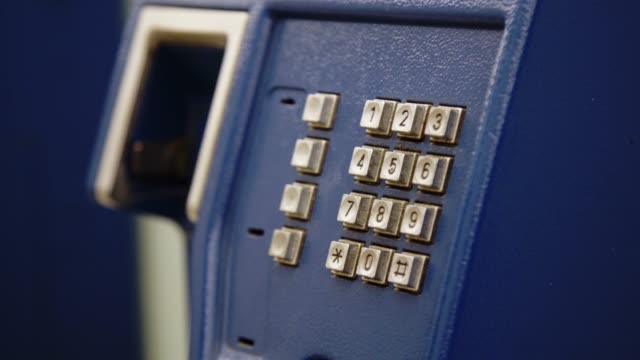 closeup hand of woman using public telephone or phone booth station. - telephone box stock videos & royalty-free footage