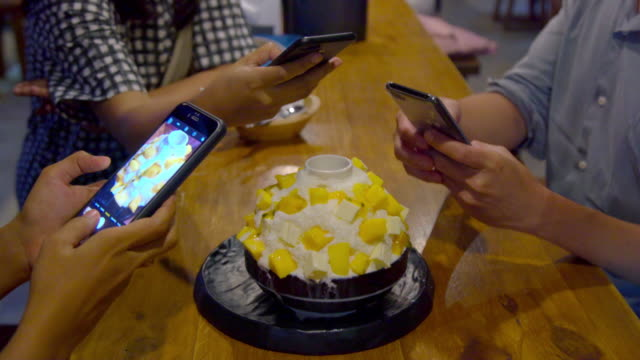 closeup hand of young asian man and woman take candid photo of mango kakigori cheese cake or ichiko kokigori a famous dessert in korea and japan and thailand for social media before eat. - peanut food stock videos & royalty-free footage