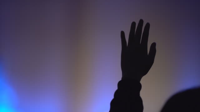 close-up hand raised at worship, silhouette shot - cristianesimo video stock e b–roll