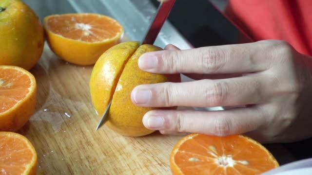 vídeos y material grabado en eventos de stock de primer plano mano cortando naranja. - parte de
