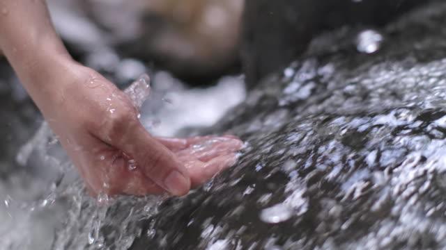 mano ravvicinata toccare un'acqua limpida di flusso fresco al rallentatore - bagnato video stock e b–roll
