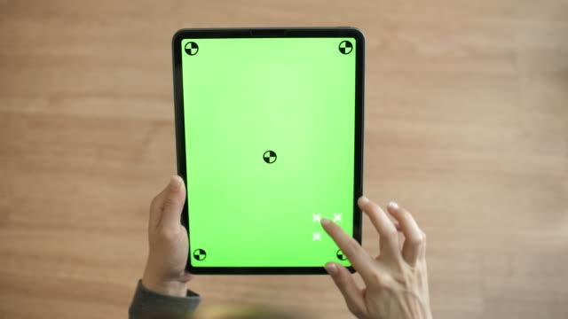vidéos et rushes de main de plan rapproché utilisant la tablette numérique avec l'écran vert sur le bureau à la maison - back lit