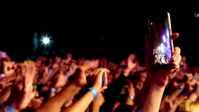 close-up - hand with a smartphone against the background of a crowd at concerts - stream stock videos & royalty-free footage