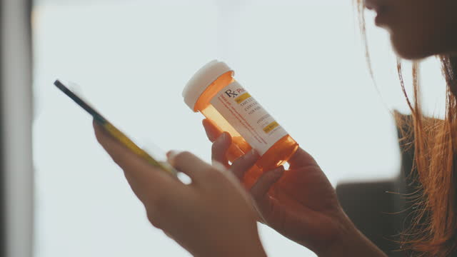 vídeos de stock, filmes e b-roll de close-up mão mulher segurando frasco de pílula e usando telefone celular - prescription medicine