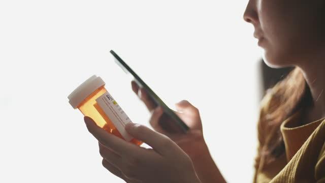 stockvideo's en b-roll-footage met close-up de vrouw die van de hand pillenfles houdt en mobiele telefoon gebruikt - medisch voorschrift