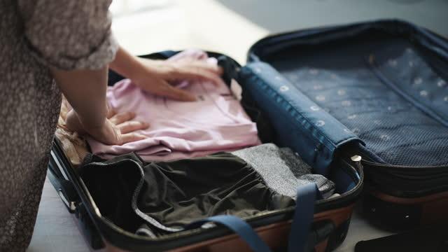 stockvideo's en b-roll-footage met close-up de vrouw van de hand die kleren in bagage thuis inpakt, voorbereidingen treffend om te reizen - pak