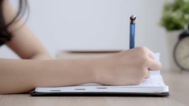 Nahaufnahme von hand Frau Studie und lernen im Wohnzimmer zu Hause, Mädchen Hausaufgaben, arbeiten am Tisch, Bildungskonzept Geschäftsfrau Notebook und Tagebuch zu schreiben.