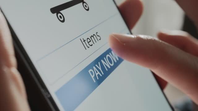 デバイス画面上で今payに触れるクローズアップハンドウーマン - プラス記号点の映像素材/bロール