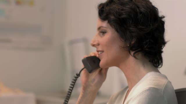 Close-up handheld pan businesswoman typing on computer keyboard, talking on telephone