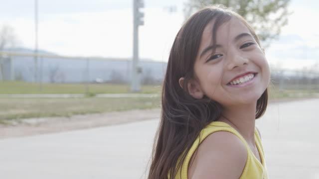 närbild handhållen shot av en söt 10-11-årig spansktalande, latin, polynesiska ung barn flicka leende tittar över axeln på våren eller sommaren utomhus - 10 11 år bildbanksvideor och videomaterial från bakom kulisserna