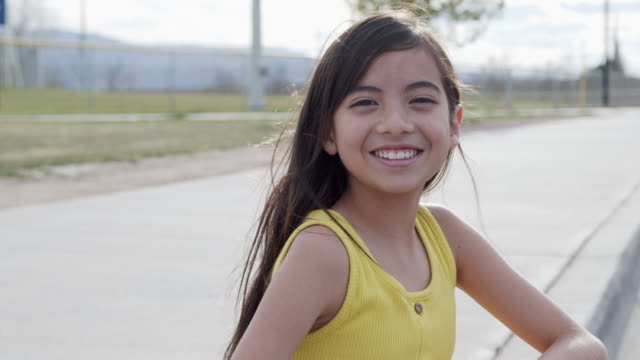 close-up handheld shot of a cute 10-11-year-old hispanic, latin, polynesian young child girl smiling looking over her shoulder in the spring or summer outdoors - pacific islanders stock videos & royalty-free footage