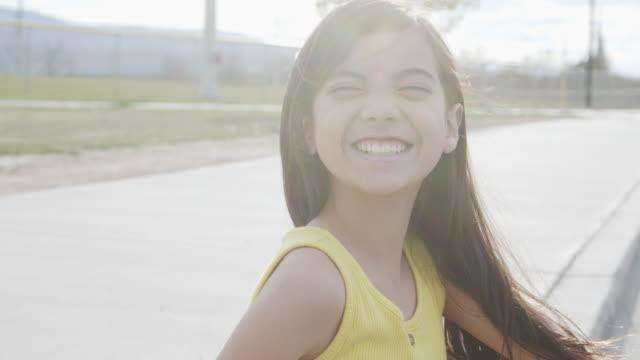 närbild handhållen shot av en söt 10-11-årig spansktalande, latin, polynesiska ung barn flicka leende gör ett ansikte och ser över axeln på våren eller sommaren utomhus - 10 11 år bildbanksvideor och videomaterial från bakom kulisserna