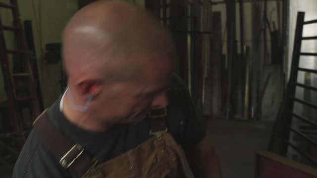 vídeos de stock e filmes b-roll de close-up handheld shot of a woodworker doing woodwork in his workshop - protetor de ouvido