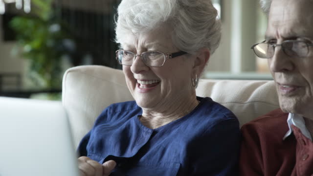 vídeos y material grabado en eventos de stock de close-up handheld shot of cheerful senior couple video conferencing through laptop computer at home - voz sobre ip