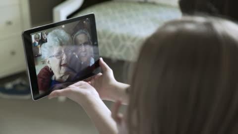 vídeos y material grabado en eventos de stock de close-up handheld shot of sisters video conferencing with grandparents through tablet computer at home - nieto