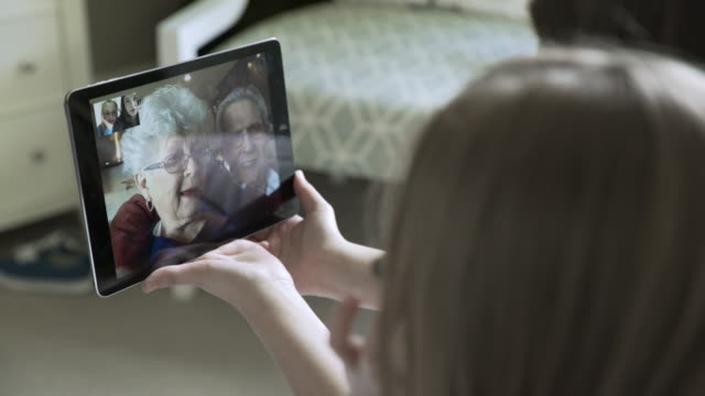 close-up handheld shot of sisters video conferencing with grandparents through tablet computer at home - grandchild stock videos & royalty-free footage