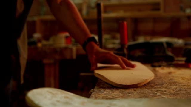 vidéos et rushes de mains rapprochées d'un charpentier vérifiant la douceur d'un bord - texture douce