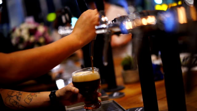 close-up. hands of bartender pouring beer from beer tap in party nightclub pub - pint glass stock videos & royalty-free footage