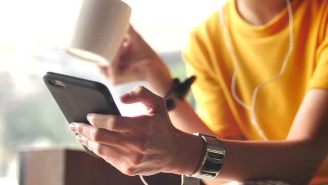 Gros plan mains de femme appréciant la musique depuis son téléphone