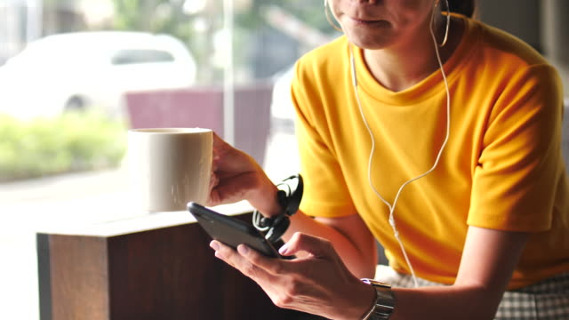 彼女の携帯電話から音楽を楽しんでいる女性のクローズ アップ手 - 朗らか点の映像素材/bロール