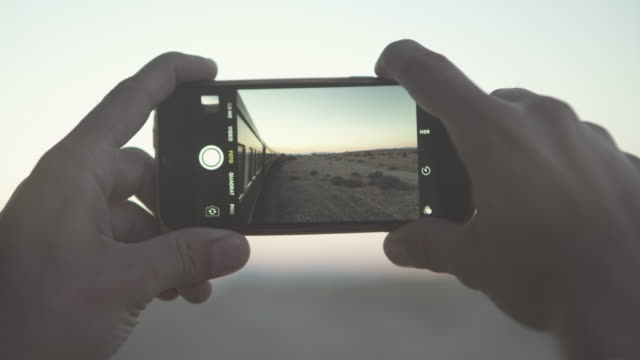 close-up hands photographing landscape through smart phone during sunset while traveling in train - swakopmund, namibia - photographing stock videos & royalty-free footage