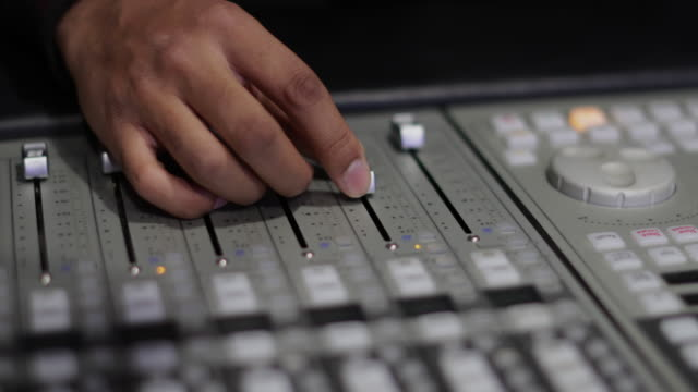 Closeup hands working a control mixer in a recording studio