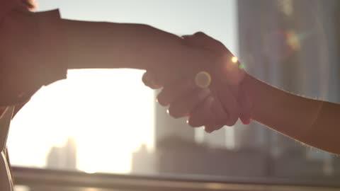 slo mo närbild handslag med solljus i city - framgång bildbanksvideor och videomaterial från bakom kulisserna